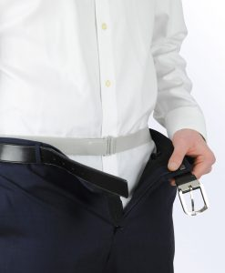 man showing Tuck-N-Stay over his shirt, but under his pants. It is invisible under clothing