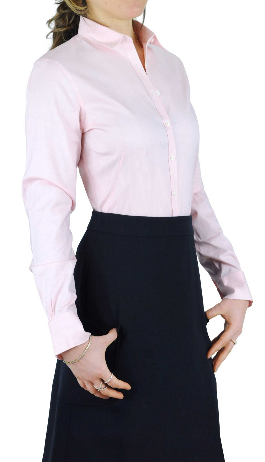 A woman wearing Tuck-N-Stay to keep this pink shirt tucked into the black skirt